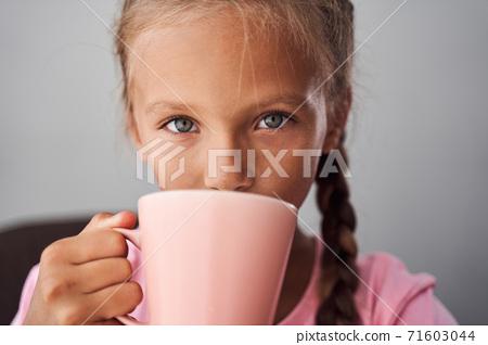 Girl enjoying of hot beverage 71603044