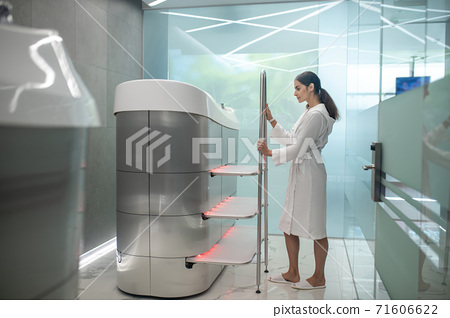 Dark-haired female in white robe standing next to hydromassage bathtub 71606622