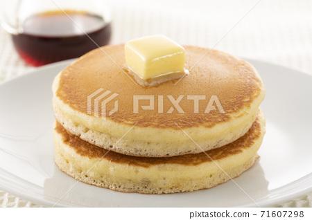 將楓糖漿撒在堆積的熱蛋糕上並吃 71607298