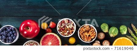 Vegan food panorama, top shot with a place for text. Fruit and vegetables, legumes, mushrooms, nuts, a flat lay header 71619046