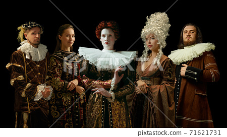 Medieval people as a royalty persons in vintage clothing on dark background. Concept of comparison of eras, modernity and renaissance. Creative collage. 71621731