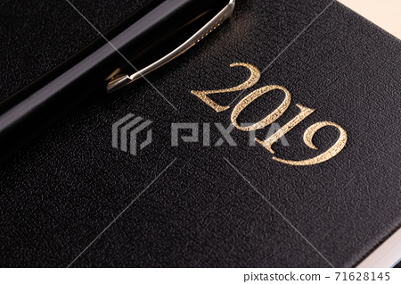 A pen on a closed black notebook diary with the inscription 2019 for doing business in the new year 71628145