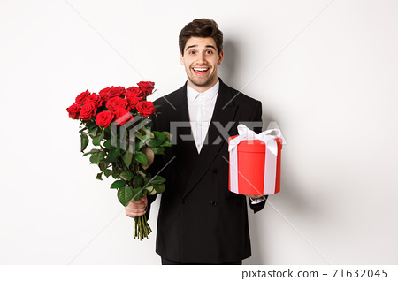 Concept of holidays, relationship and celebration. Image of handsome smiling guy in black suit, holding bouquet of red roses and giving present on new year, white background 71632045