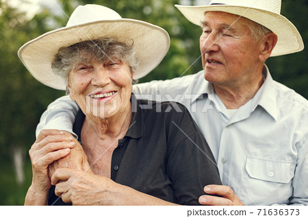 Beautiful old couple spend time in a summer garden 71636373