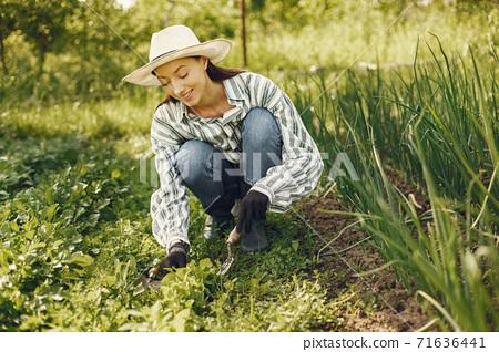 Woman in a hat working in a garden 71636441