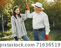 Portrait of senior man in a hat gardening with granddaugher 71636519