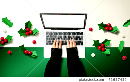 Person using a laptop computer with Christmas holly berries 71637432