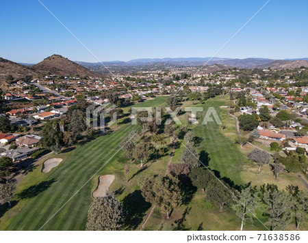Aerial view of golf in upscale residential neighborhood during autumn season 71638586