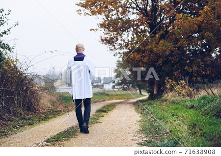 A christian priest is walking on a country road. 71638908