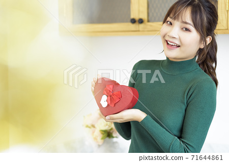 Young woman with gift box 71644861