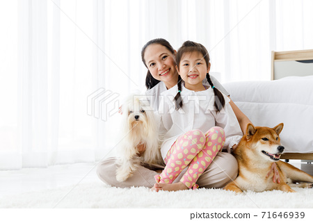 Happy Asian mother and daughter sitting on bedroom floor with Maltese and Shiba Inu. 71646939