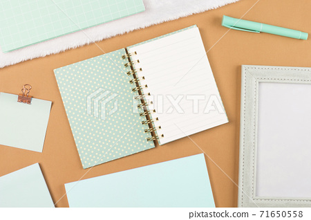 flat lay mint green stationery on work desk in brown pastel background 71650558