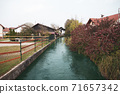 Small river goes in village between houses, autumn season. 71657342