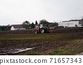 Red tractor plowing field in autumn season in the village 71657343