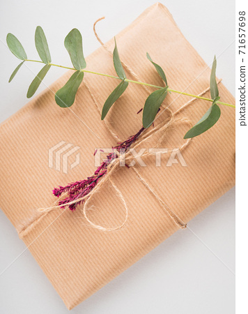 Gift boxes wrapped in craft paper with dried flowers 71657698