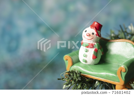 A snowman model sitting on a green sofa with a blurry bokeh background 71681402
