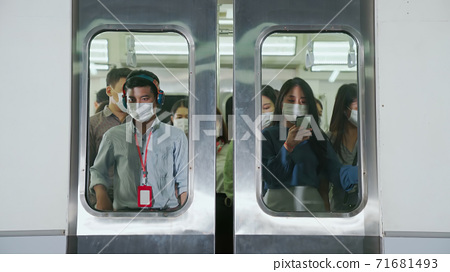 Crowd of people wearing face mask on a crowded public subway train travel 71681493