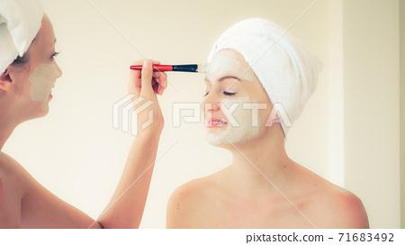 Beautiful woman having a facial treatment at spa. 71683492