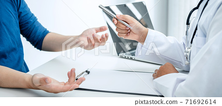 Doctor hold pen and patient discussing something in medical clinic 71692614