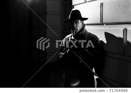 dark dramatic silhouette of a man in a hat Smoking a cigarette on the street at night 71704986