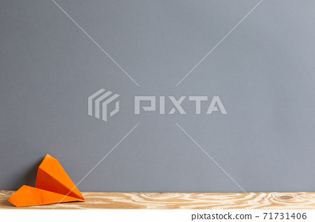 Orange paper plane on wooden table. Gray background copy space 71731406