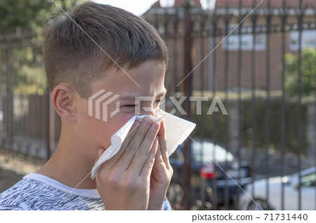 Teen boy blows his nose in a paper handkerchief on a background of fence and cars. Flu and allergies to exhaust fumes and pollen 71731440
