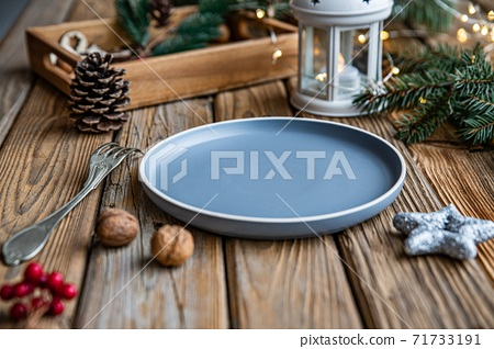 Christmas decoration. Empty plate, fork, nuts, wooden tray, lantern and green twig. 71733191