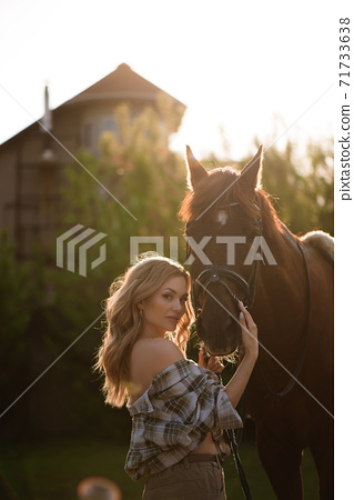 Portrait of girl inplaid shirt with black horse in the horse farm. 71733638