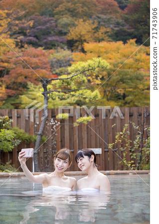 兩名年輕婦女在露天浴場拍照以秋葉為背景 71743906