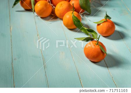 Fresh tangerines on blue wooden table 71751103