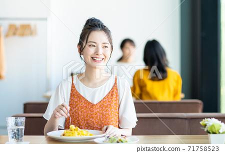 年輕女子在一家餐館吃午餐 71758523