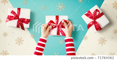 Person making Christmas gift boxes 71764362