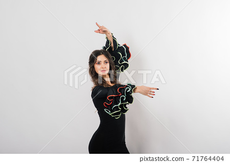 Portrait of beautiful young woman dancing flamenco in studio 71764404