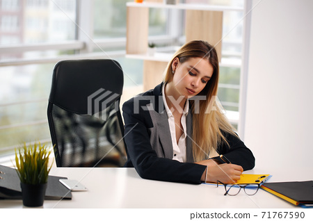 Portrait of cheerful businesswoman writing on contract sitting at desk in office. The concept of profession and leisure 71767590