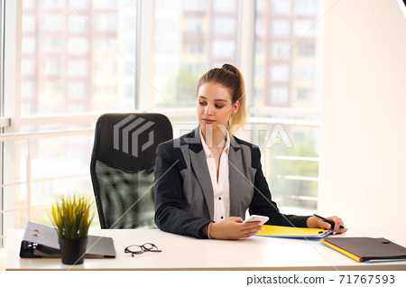 girl in a black businesswoman jacket works in a bright office 71767593