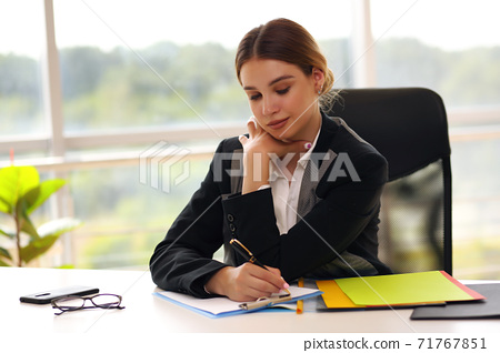 Young happy smiling businesswoman working at office 71767851