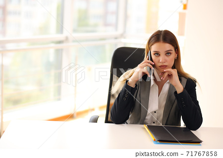 young girl talking on the phone in the office 71767858