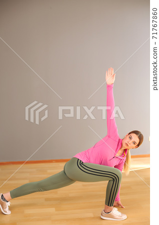 Young sport happy sexy blonde girl in green leggings and pink top doing yoga exercise 71767860