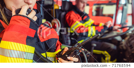 Fire fighter woman on duty using the radio 71768594