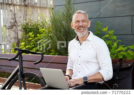 Happy guy. Successful modern middle aged businessman in stylish suit smiling aside while working on his laptop, sitting on the bench outdoors with a bicycle next to him 71770222