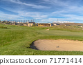 Scenic view of golf course and homes against blue sky and clouds on a sunny day 71771414