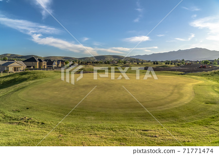 Scenic golf course landscape against houses and mountain under sky and clouds 71771474