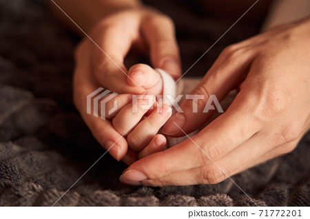 Woman hands holding hands of her newborn 71772201
