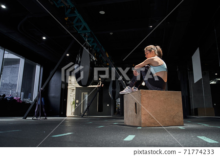 Tired woman sitting at the wooden jumping box 71774233