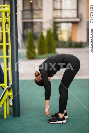 Sportswoman stretching muscles making functional training, makes a slope. 71775803