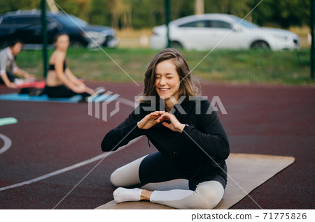 Young fit woman in sportswear trains outdoors on the playground. 71775826