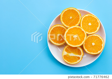 Sliced oranges on blue background. High vitamin C, Juicy and sweet. 71776462