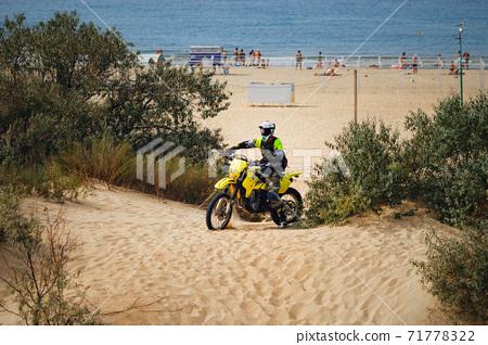 off-road motorcycle enduro motocross rider on sand dune, sea beach background 71778322