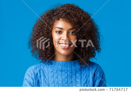 Close-up portrait lovely young african-american woman with curly, afro haircut, smiling and looking camera with happy pleasant expression, enjoying winter holidays, wearing sweater, blue background 71784717