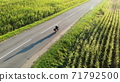 motorcycle riding by country road on sunset, beautiful adventure travel footage shot from drone, top aerial 71792500